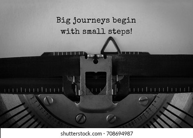 Text Big journeys begin with small steps typed on retro typewriter