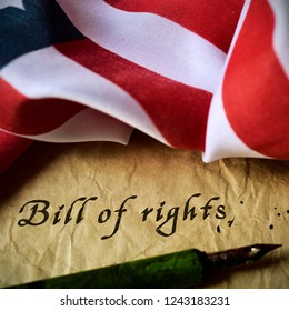 the text bill of rights written in an old piece of paper with a nib pen, and a flag of the united states,