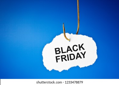 Text Black Friday hanging on a fishing hook over blue background. Beware of the Black Friday sale trap concept.