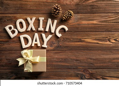 Text BOXING DAY and gift box on wooden background