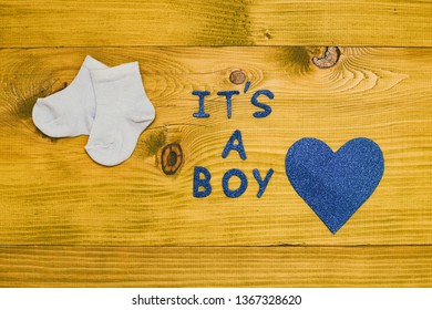 Text it's a boy with baby boy socks and heart shape on wooden table.Toned photo.