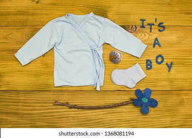 Text it's a boy with baby supplies and flower on wooden table.Toned photo.