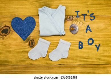 Text it's a boy with baby supplies and heart shape on wooden table.Toned photo.