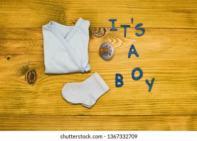 Text it's a boy with baby supplies on wooden table.Toned photo.