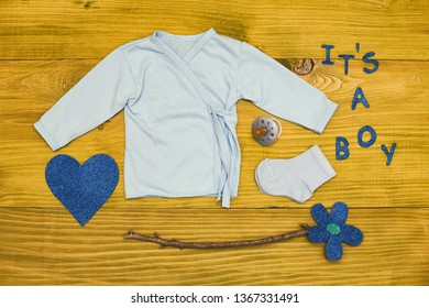 Text it's a boy with baby supplies,heart shape  and flower on wooden table.Toned photo.