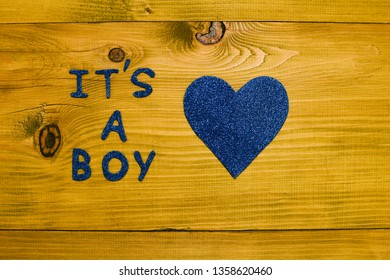 Text it's a boy and heart shape on wooden table.Toned photo.