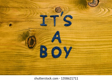 Text it's a boy on wooden table.Toned photo.
