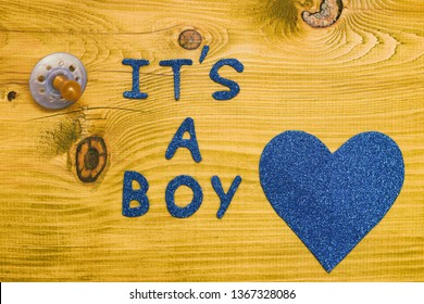 Text it's a boy with pacifier  and heart shape on wooden table.Toned photo.