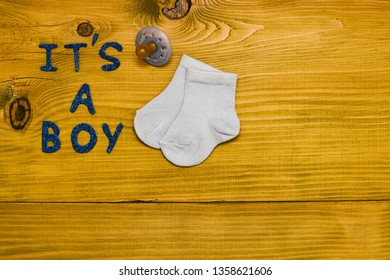 Text it's a boy with pacifier and little baby socks on wooden table.Toned photo.
