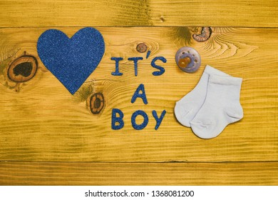 Text it's a boy with pacifier, little baby socks and heart shape on wooden table.Toned photo.