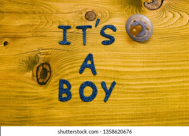 Text it's a boy with pacifier on wooden table.Toned photo.