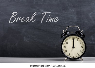 Text Break Time handwritten with white chalk on a blackboard and retro alarm clock