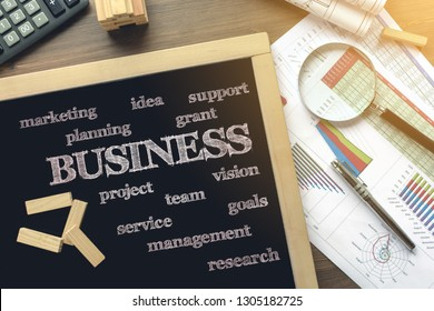 Text Business and other on the blackboard on the desk with office business accessories