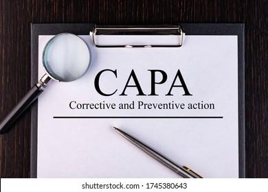 Text CAPA. Concept image of Business Acronym CAPA Corrective and Preventive action. is written on a notebook with a pen and a magnifying glass lying on the table. Business concept.