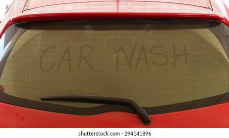 text of car wash on back mirror dirty car
