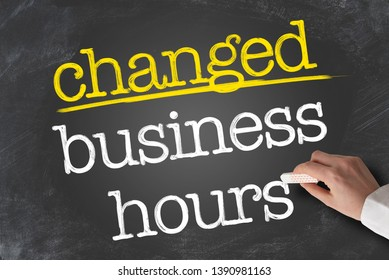 text CHANGED BUSINESS HOURS written on blackboard with hand holding piece of chalk