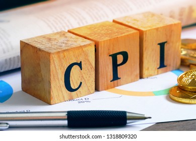 "Text ""CPI"" on wood cube with gold bar and newspaper on the table, economic data concept"