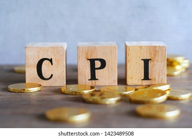 "Text ""CPI"" on wood cube with gold coins on the table, economic data concept."