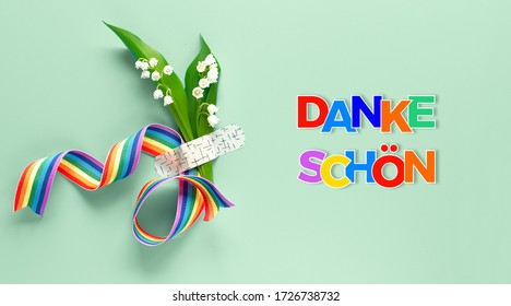 """Text """"Danke shon"""" in German language means """"Thank you"""". Rainbow ribbon, lily of the valley flowers. Bouquet attached to background with medical aid patch. Creative flat lay on green mint background."""