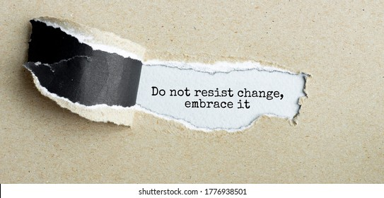 The text Do not resist change embrace it appearing behind torn brown paper