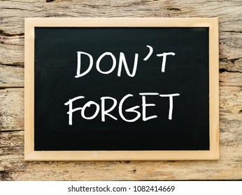 "text ""don't forget"" on black chalkboard with wooden background. meeting remind reminder note concept"