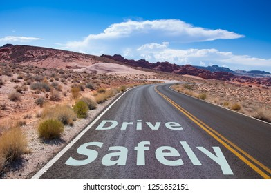 """The text """"DRIVE SAFELY"""" written on a empty road in the desert of Nevada before the street turns right"""