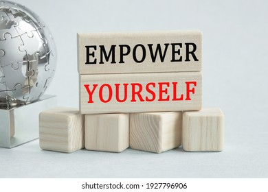 Text EMPOWER YOURSELF. Globe and wooden cubes on a gray background. The concept of world business, marketing, finance.
