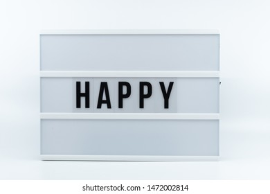 Text in english spelling' happy' on a lightbox against white background.