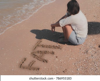 text fat on sand at beach.and sad girl sitting near that word.look like worry about weigh