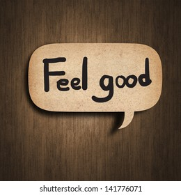 Text feel good on the speedch bubble paper on wood background