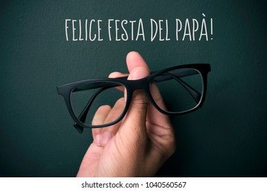 the text felice festa del papa, happy fathers day in italian, and the hand of a young caucasian man holding a pair of eyeglasses depicting a man face, on a dark green background