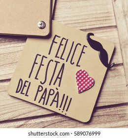 the text felice festa del papa, happy fathers day written in italian in a brown piece of paper, a mustache and a heart, on a rustic wooden background