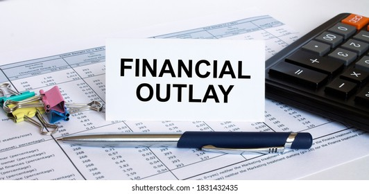 Text Financial Outlay on white card with blue metal pen, calculator and paper clips on financial table. Business and financial concept