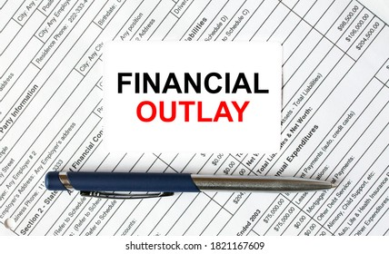 Text Financial Outlay written on a business card lying on financial tables with a blue metal pen. Business and financial concept
