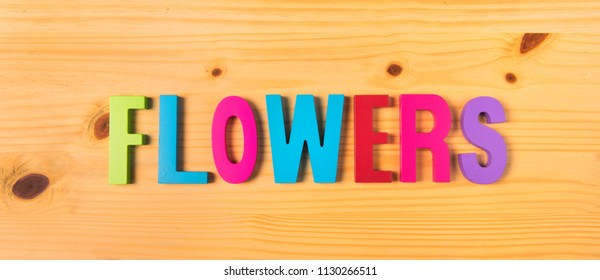 Text flowers word in colorful wooden letters on wood