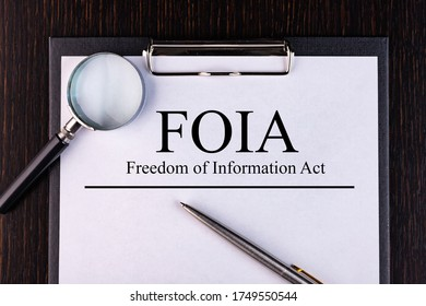 Text FOIA Act. is written on a notebook with a pen and a magnifying glass lying on the table. Business concept.