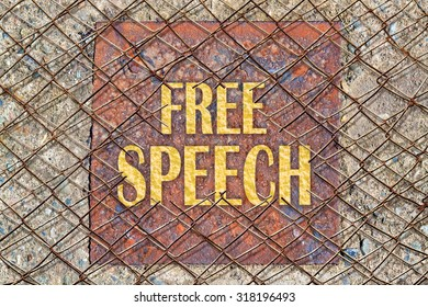 Text Free Speech in golden color under a broken wire fence