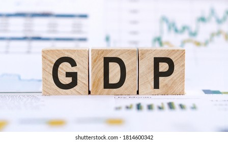 """Text """"GDP"""" - gross domestic product - on wooden cubes on financial document and charts data. Economic data concept."""