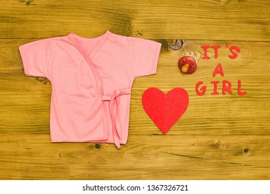 Text it's a girl with baby supplies and  heart shape and on wooden table.Toned photo.