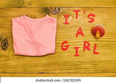 Text it's a girl with baby supplies  on wooden table.Toned photo.