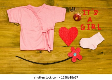 Text it's a girl with baby supplies,heart shape and flower on wooden table.Toned photo.