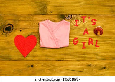 Text it's a girl with baby supplies,heart shape  on wooden table.Toned photo.