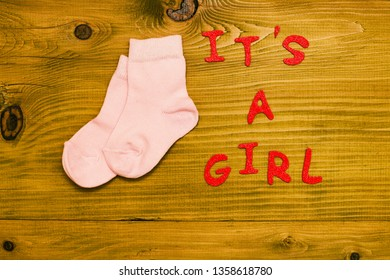 Text it's a girl with  little baby girl socks on wooden table.Toned photo.