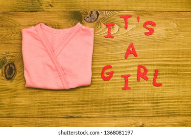 Text it's a girl with little baby t-shirt  on wooden table.Toned photo.