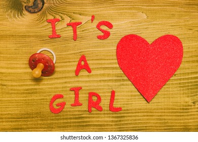 Text it's a girl with pacifier and heart shape on wooden table.Toned photo.