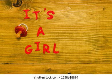 Text it's a girl with pacifier on wooden table.Toned photo.