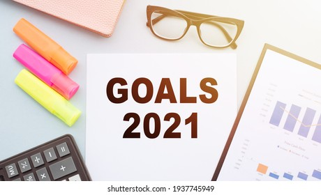 The text GOALS 2021 on office desk with calculator, markers, glasses and financial charts.