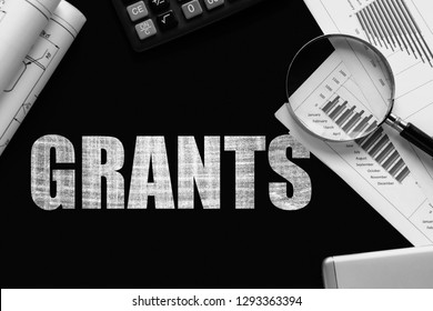 Text Grants  on chalkboard with graphs, tables, calculations, calculator
