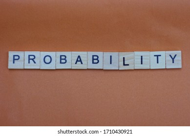 text from a gray long word probability of small wooden letters on a brown table
