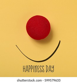 the text happiness day, a red clown nose and a smile drawn on a yellow background
